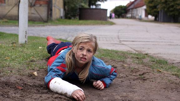 Friederike (Flora Li Thiemann) - mit Gipsverband am Arm - liegt am Boden.