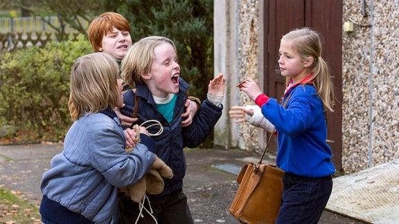 Finn Fiebig (als Fabian) und  Emil von Schönfels (als Oliver) halten Luca Johannsen (als Jonathan) fest.  Rechts steht Flora Li Thiemann (als Friederike).