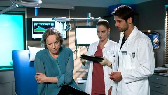 Julia (Mirka Pigulla, M.) und Niklas (Roy Peter Link, r.) sagen Silke Kirschbaum (Claudia Geisler-Bading, l.), dass sie einen Tumor hat, der entfernt werden muss.