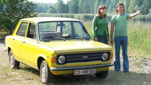"""Elke (Katharina Wackernagel) und Gregor (Peter Schneider) stehen mit einem """"Lada"""" an einem See."""