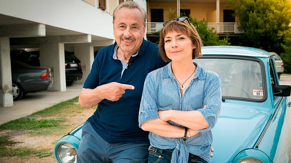 """Schauspieler Wolfgang Stumph und Claudia Schmutzler in Italien, Hotel La Romantica, Manerba del Garda. Sie sitzen auf einem himmelblauen !trabant""""."""