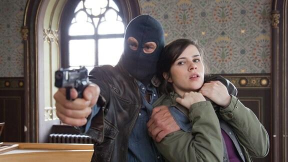 Kira Dorns (Nora Tschirner) Hals wir von einem Geiselnehmer (Wolfgang Maria Bauer) umschlungen. In der rechten Hand hat er eine Pistole. deren Mündung nach vorn zielt.