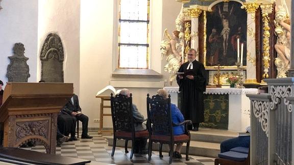Ein Priester steht vor einem Altar und spricht zu einem älteren Ehepaar.