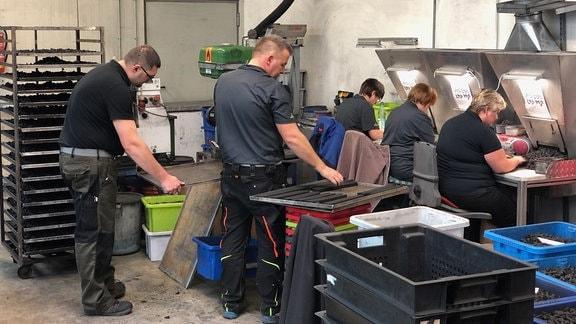 Mitarbeiter einer Manufaktur stellen Räucherkerzen her.