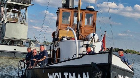 """Der Dampfschlepper """"Woltman"""" im Hamburger Hafen wurde 1904 auf der Roßlauer Schiffswerft gebaut, bis 1976 im Dienst im Hamburger Hafen, dann von Liebhabern vor dem Schrottplatz gerettet. Hans Friedrich (links) und Dieter Herrmann (beide vorne an Deck) waren Ingenieure auf der Roßlauer Schiffswerft."""