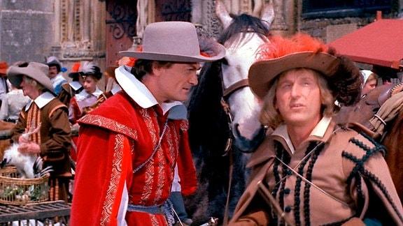 """François de Capestang (Jean Marais, l.), """"Le Capitan"""" genannt und sein Gefolgsmann Cogolin (Bourvil) stehen vor einem Pferd. Im Hintergrund Markttreiben."""