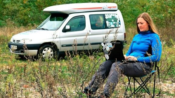Anja Müller (39) sitzt vor ihrem Auto in freier Natur; auf ihren Knien ein Notebook