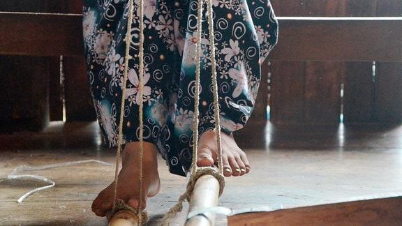Auch die Füße kommen am Webstuhl zum Einsatz.