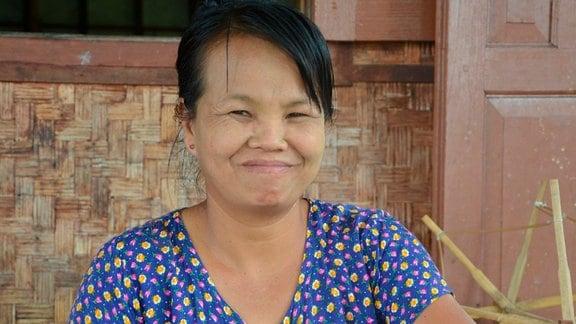 Im Webhaus von In Paw Khone zeigt Vorführerin Ohe Mya den Touristen, wie sich aus Lotos Garn gewinnen lässt.