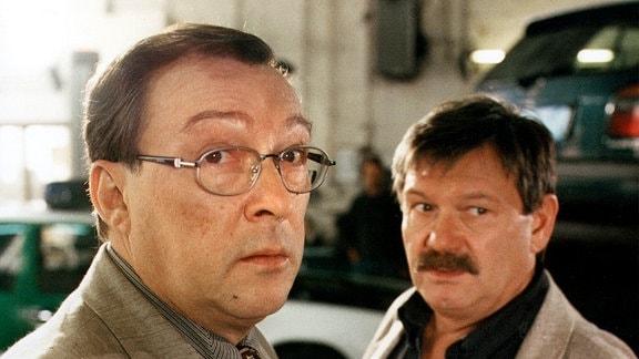 Hauptkommissar Herbert Schmücke (Jaecki Schwarz, links) und Hauptkommissar Herbert Schneider (Wolfgang Winkler) blicken in Richtung Kamera.