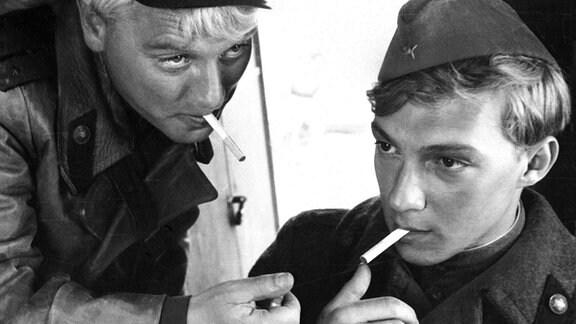 Gregor (Jaecki Schwarz, re.) mit eiber Zigarette im Mund.  Sascha (Alexej Ejboshenko) zündet sie an.