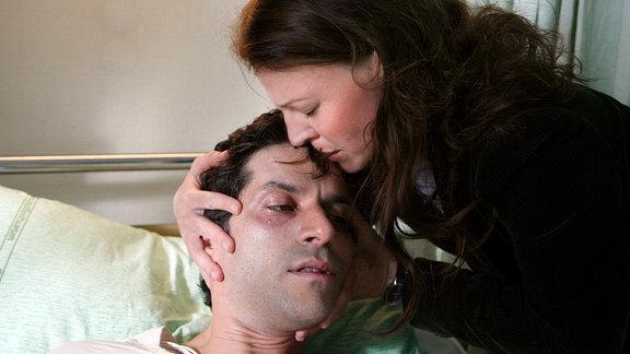 Tinka (Maria Simon) am Bett ihres im Sterben liegenden Mannes Carlo (Pasquale Aleardi), der seine Liebe zu Melanie gesteht.