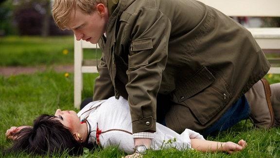 Melanie (Anna Fischer) ist im Park beim Spaziergang mit Ludwig (David Zimmerschied) zusammengebrochen.