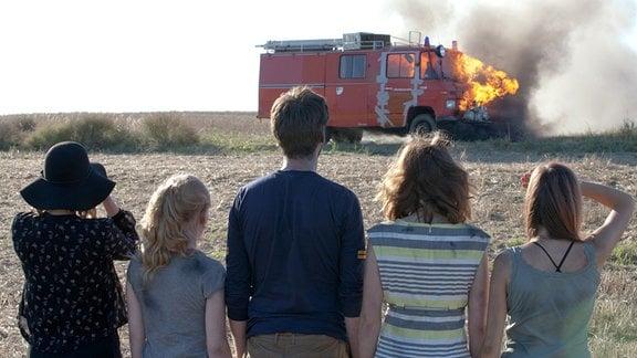 Wie geht es nun weiter? Das Feuerwehrauto steht in Flammen (von links nach rechts): Die Tramperin Charlotte (Morgane Ferru), Philomena (Gro Swantje Kohlhof), Rick (Sebastian Fräsdorf Rick), Laura (Karin Hanczewski) und Kristin (Claudia Eisinger)