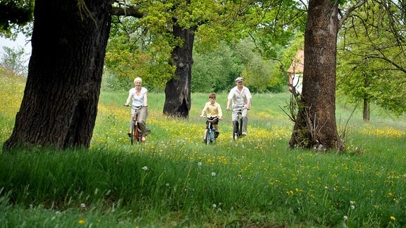 Die Darsteller Finn Hänsch, Olga Sidorowa und Friedrich Meyer fahren Fahrrad.