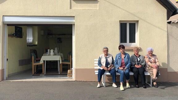 Vier ältere Frauen sitzen nebeneinander auf einer weißen Bank, die vor einem Haus unter einem Fenster steht.