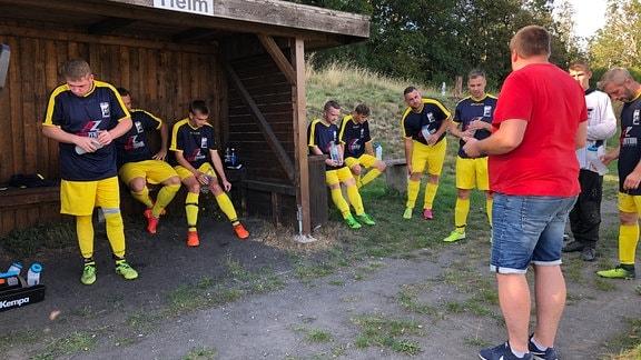 Die Mitglieder eines Fußballteams wenden sich stehend und sitzend ihrem Trainer zu. Sie tragen gelb-dunkelblaue Trikots.