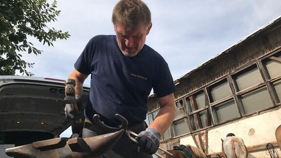 Ein Mann schmiedet ein Hufeisen indem er es mit dem Hammer sachgerecht geformt und bearbeitet. Zwei Pferde stehen im Hintergrund.