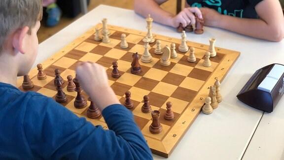 Zwei Jungen spielen Schach. Ein Junge in blauem Pullover ist am Zug. Sie stoppen die Zeit mit einem Gerät.