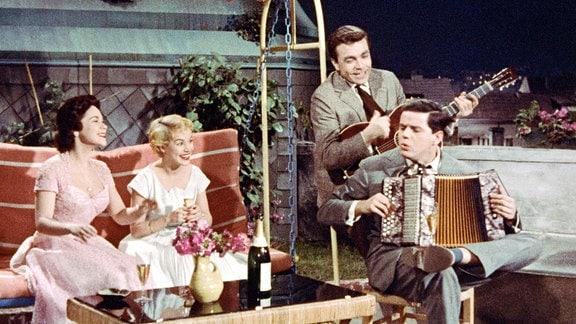 Zwei Frauen sitzen in einer Hollywod-Schaukel, ihnen gegenüber sitzen zwei Männer.