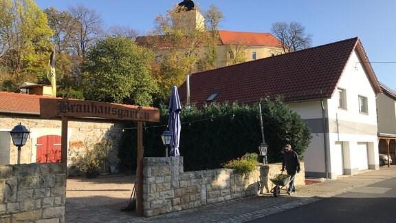 """Der Eingang zum Fischrestaurant unter einem hölzernen Torbogen mit der Aufschrift """"Brauhausgarten""""."""