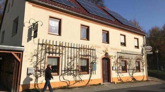 """Ein gelbes Haus mit der Aufschrift """"Gasthaus Hirschstein"""" über der Tür."""