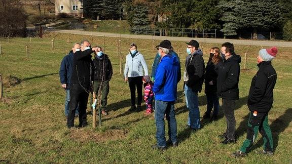 Eine Gruppe von Menschen steht auf einer Wiese, auf der junge Apfelbäume gepflanzt sind.