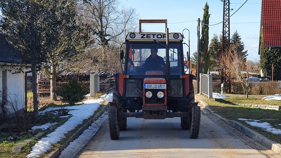 Ein Traktor auf einer schmalen Straße im Dorf.