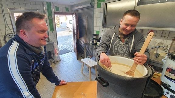 Zwei Männer in einer Küche. Einer stützt sich lächelnd auf einem Tisch ab, während der andere in einem Topf mit heller Flüssigkeit rührt.