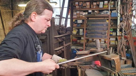 Ein Schmied bei der Arbeit in seiner Werkstatt.