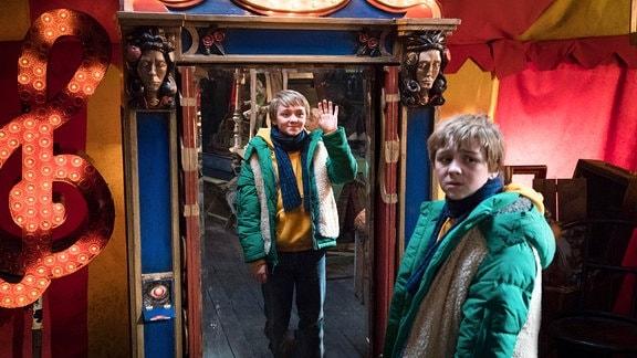 Der Doppelgänger Frido II (Luis Vorbach) winkt aus dem Spiegel Frido (Luis Vorbach) zu.