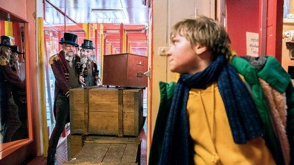 Frido (Luis Vorbach) versteckt sich hinter dem Schrank, während der Spiegelkabinettbesitzer (Butz Buse) eine Kiste verschiebt.