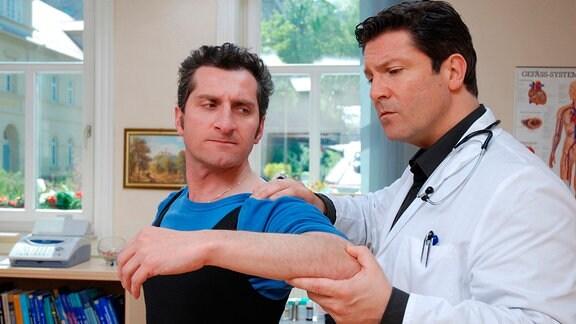 Dr. Kleist (Francis Fulton Smith, r.) untersucht die Schulter von dem Artisten Stefano Piranelli (Tim Seyfi, l.).
