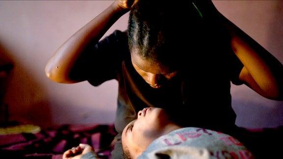 Aster tastet sich beim Flechten ihrer Zöpfe durchs Haar und ihre kleine Tochter leistet ihr Gesellschaft.