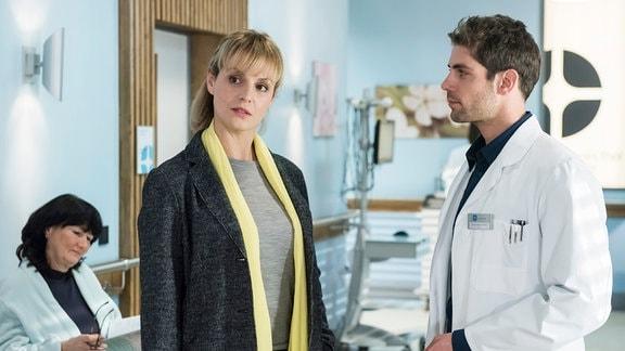 Die Neurochirurgin Dr. Lea Peters (Anja Nejarri, 2.v.l. mit Komparsin, l.) ist eigentlich nur für einen Vortrag angereist. Doch dann übernimmt sie spontan die OP eines Patienten mit Wirbelbruch (mit Roy Peter Link, r.).