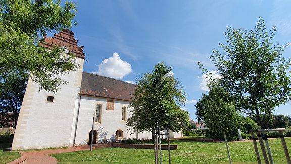 Eine kleine, weiße Kirche mit rotem Dach auf einer Wiese.