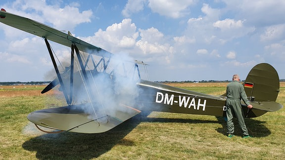 Ein grünes Flugzeug auf dem Boden, dichter Rauch steigt aus dem Cockpit auf.
