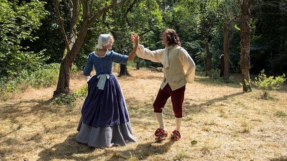 Kammerzofe Lisbeth (Luise von Finckh) lernt Johann (Jonas Lauenstein) die höfischen Tänze.