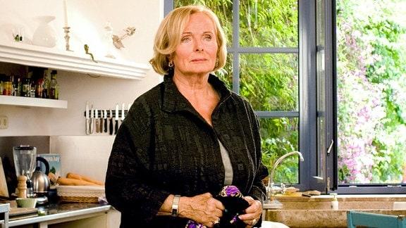 Eine Frau steht nachdenklich in einer Küche und hält ein Stück Stoff in der Hand.