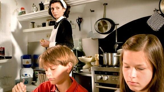 Zwei Kinder sitzen in einer Küche am Tisch, eine Frau im Hintergrund schaut nachdenklich in die Ferne.