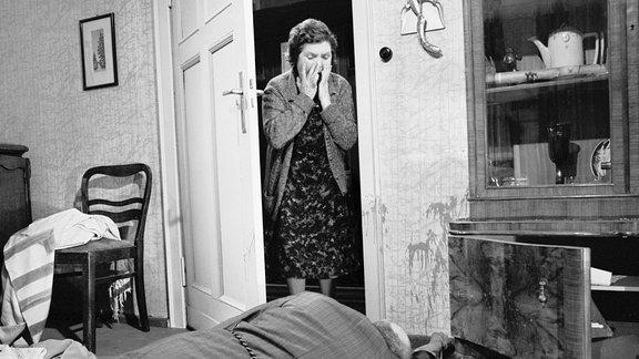 Rentner Wilhelm Hoppe liegt tot am Boden, Nachbarin Frau Verchow schaut zur Tür herein.
