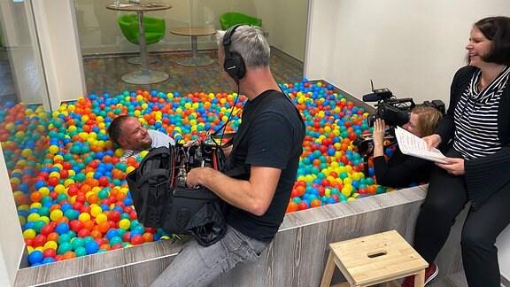 Christian Grötsch liegt bei einem Interview im Bällebad