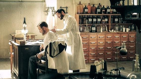 Robert Koch (Justus von Dohnányi, l.) erprobt sein neuartiges Tuberkulose-Heilmittel an sich selbst: er lässt sich von Ehrlich (Christoph Bach, r.) Tuberkulin spritzen