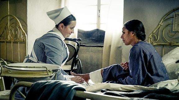 Wärterin Stine (Monika Oschek, l.) kümmert sich um die pockenkranke Inderin Rajani (Amy Mußul).