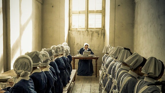 Oberin Martha (Ramona Kunze-Libnow, M.) liest in der Zeitung über den Boykott der Charité.