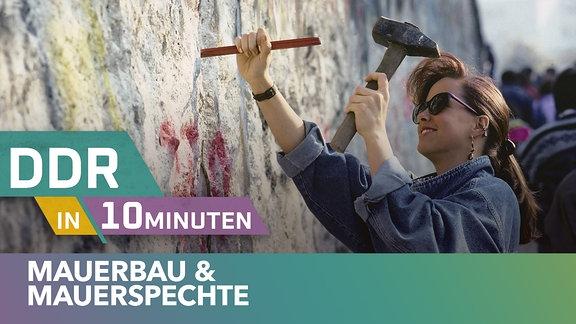 Eine Frau mit Pferdeschwanz und Sonnenbrille mit einem großen Hammer an der Berliner Mauer