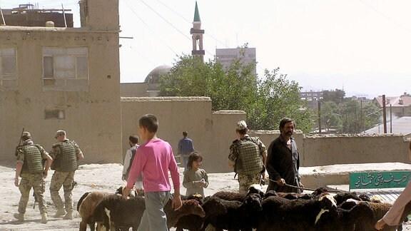 Mehrere Personen, darunter Soldaten, und eine Herde Ziegen laufen über eine Straße in einer afghanischen Stadt