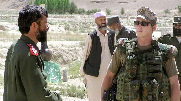 Zwei Personen in Armeeuniformen sprechen miteinander.