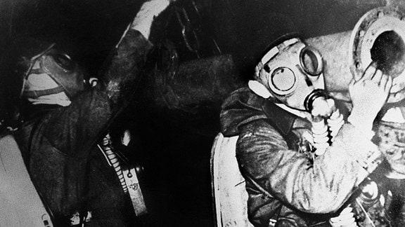Rettungskräfte mit Atemschutz im Schacht.