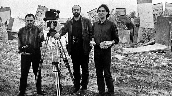 Drei Männer neben einer Kamera